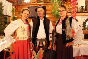 Goralische Live-Musik: Aneta, Bogusław und Katarzyna in traditionellen Trachten. Bogusław hält das goralische Kontrabass in der linken Hand. © Natalie Junghof